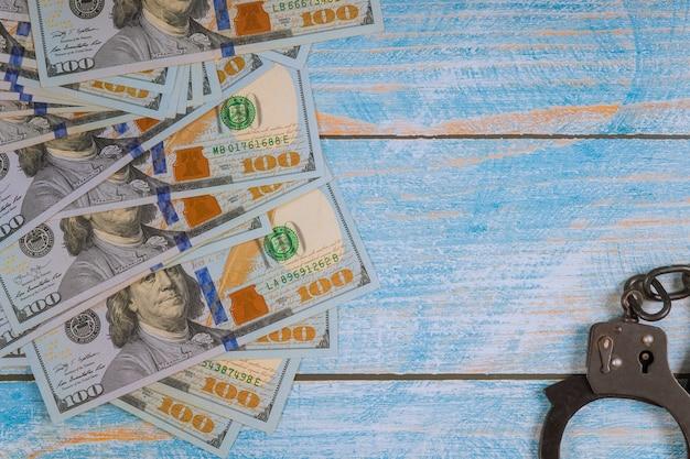 Handboeien voor de arrestatie van criminelen, amerikaanse dollarbiljetten voor financiële misdrijven, corruptie.