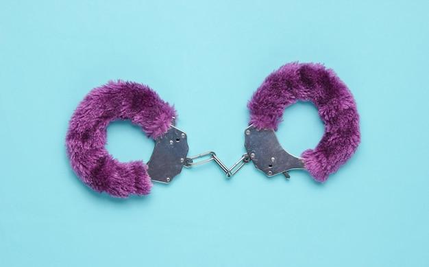 Handboeien voor seksspelletjes op blauwe achtergrond. seksueel bdsm-speeltje. liefde concept.