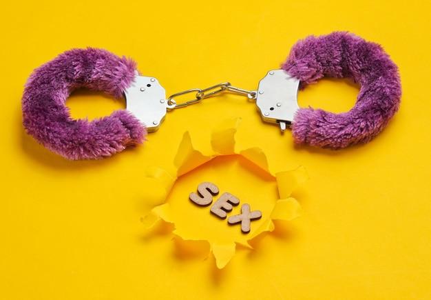 Handboeien voor seksspelletjes op gele achtergrond met gescheurd gat en woordseks. seksueel bdsm-speeltje. fetisj, erotisch concept.