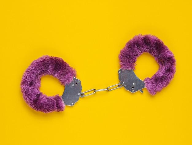 Handboeien voor seksspelletjes op gele achtergrond. seksueel bdsm-speeltje. fetisj, erotisch concept.