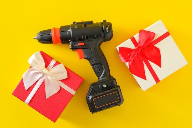 Handboormachine op accu, handbatterij schroevendraaier en geschenkverpakkingen. concept van geschenkverrassing voor mannen, bovenaanzicht