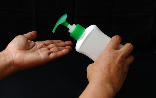 Handdesinfecterend middel dat op een zwarte achtergrond wordt geïsoleerd