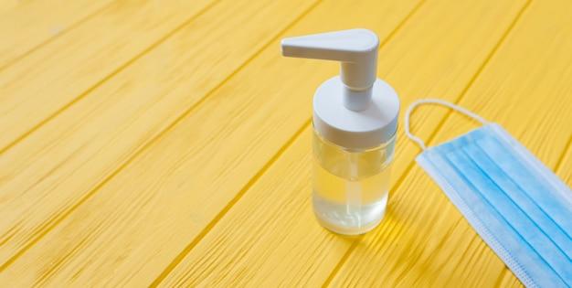 Handdesinfecterende fles en ademhalingsgezichtsmasker op gele houten achtergrond. stop coronavirus concept banner