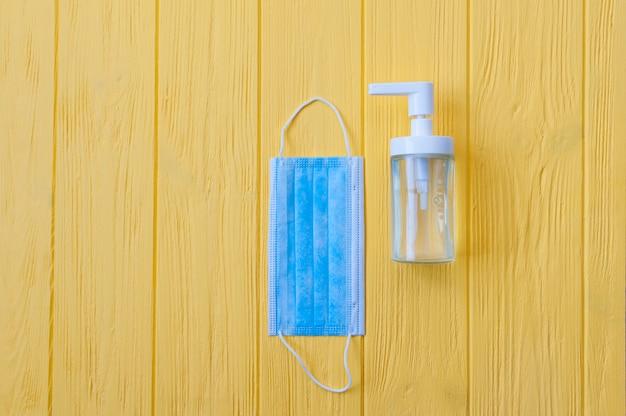 Handdesinfecterende fles en ademhalingsgezichtsmasker op gele houten achtergrond. stop coronavirus concept