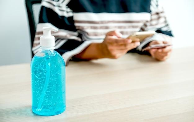 Handdesinfecterende gel op houten tafel zakenvrouw hand creditcard voor online winkelen vanuit huis, betaling e-commerce, internetbankieren, zakgeld met smartphone voor de volgende vakantie.
