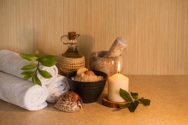 Handdoek, cosmetische massageolie, vers blad, zeezout met schelpen en kaars