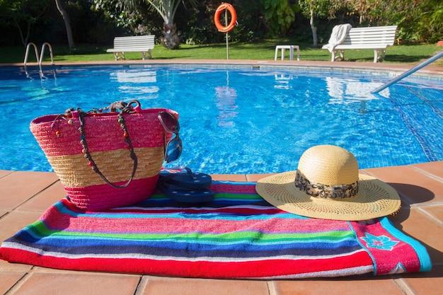 Handdoek en badaccessoires aan de kant van blauw zwembadwater