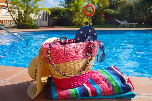 Handdoek en badaccessoires aan de kant van het blauwe zwembad