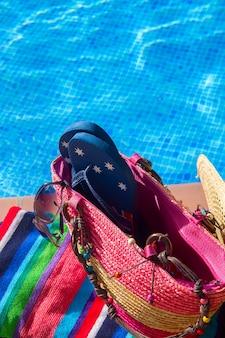 Handdoek en badaccessoires dichtbij het zwembad van dichtbij