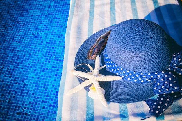 Handdoek en zomerhoed met schelpen in de buurt van water van het zwembad, retro afgezwakt