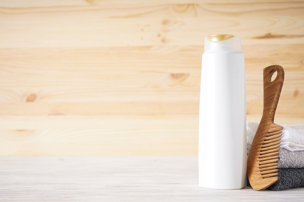 Handdoek, haarborstel en shampoo op een houten ondergrond, ruimte voor tekst.