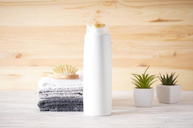 Handdoek, haarborstel, shampoo en vetplanten op een houten ondergrond