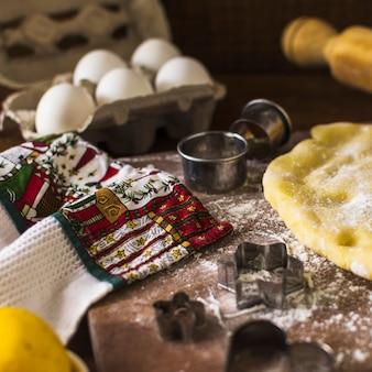 Handdoek in de buurt van cookie cutters en deeg