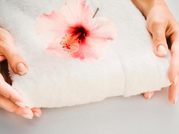Handdoek in de hand gehouden met bloem op de top