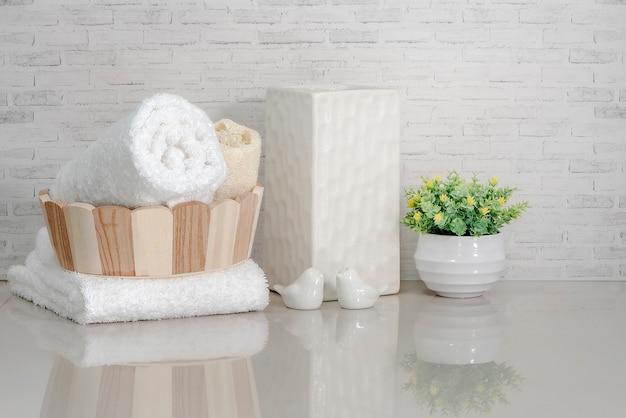 Handdoek in houten emmer met keramische vaas, keramische vogel en kamerplant