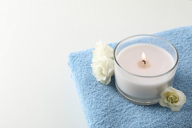 Handdoek, kaars en eustoma op wit, kopieer ruimte. spa concept
