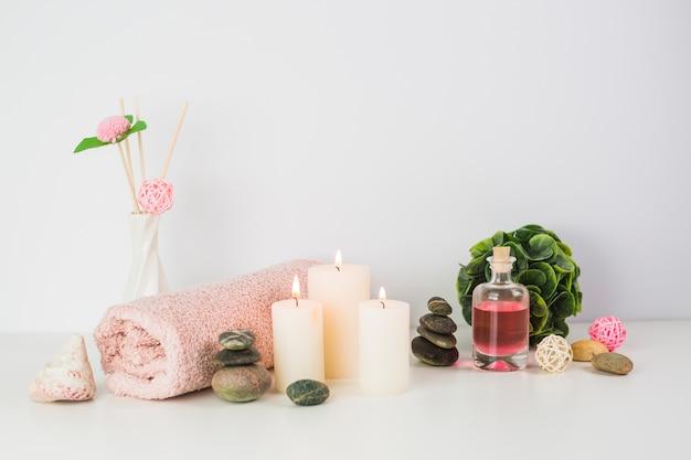 Handdoek; kaarsen; olie en spa stenen op witte ondergrond