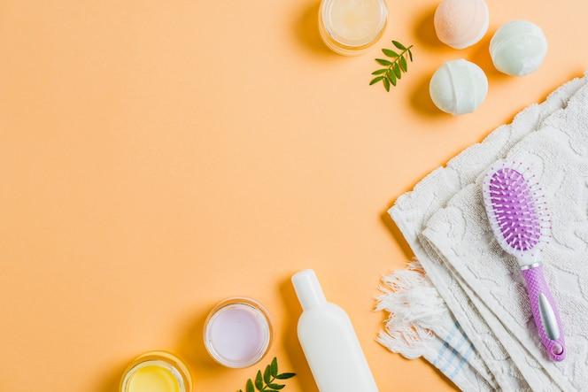 Handdoek; moisturizers; haarborstel en bad bom op gekleurde achtergrond