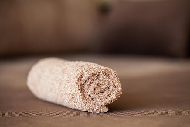 Handdoek op bruin bed met exemplaarruimte in woonkamer.