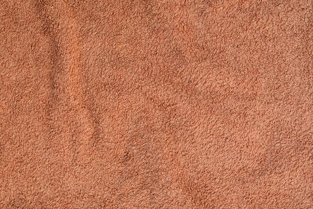 Handdoek van badstof met textuur en plooien. zandkleur