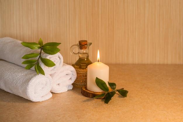 Handdoeken, cosmetische massageolie, bladeren en brandende kaars op een houten standaard