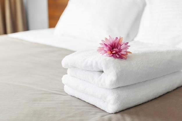 Handdoeken en bloem op bed in hotelkamer