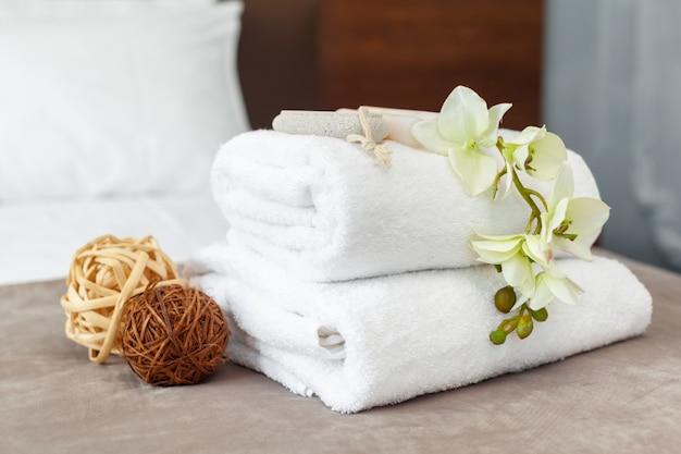 Handdoeken en bloemen op bed in de hotelkamer