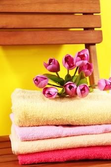 Handdoeken en bloemen op houten stoel