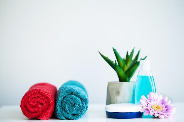 Handdoeken en douchegel op witte tafel met kopie ruimte op bad kamer achtergrond.