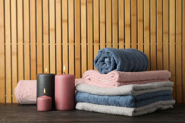 Handdoeken en kaarsen op houten tafel op bamboe, ruimte voor tekst