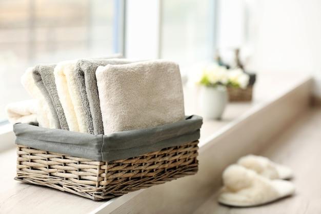 Handdoeken in rieten mand met bloemen op vensterbank