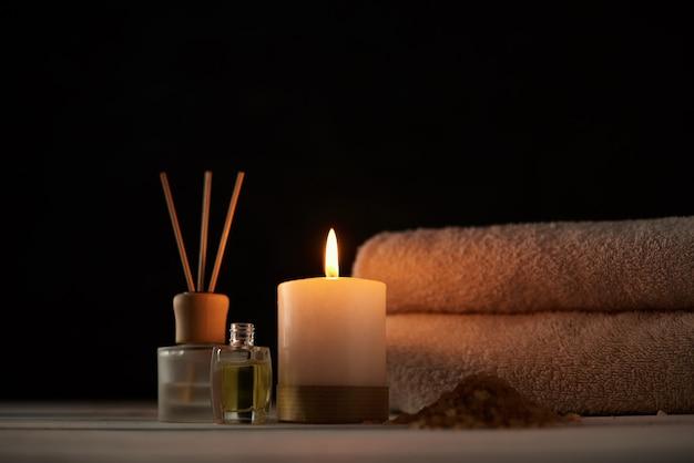 Handdoeken, kaars en massageolie op witte lijst
