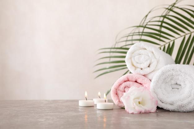 Handdoeken, kaarsen en bloemen op grijze achtergrond, ruimte voor tekst