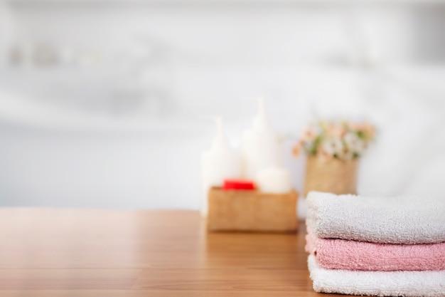 Handdoeken op houten bovenste tafel met kopie ruimte op wazig badkamer.