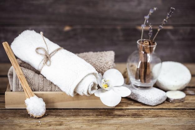 Handdoeken op houten dienblad en glazen pot met kaneelstokjes en lavendel