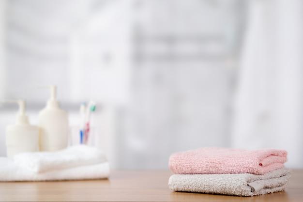 Handdoeken op houten tafel met kopie ruimte op wazig badkamer.