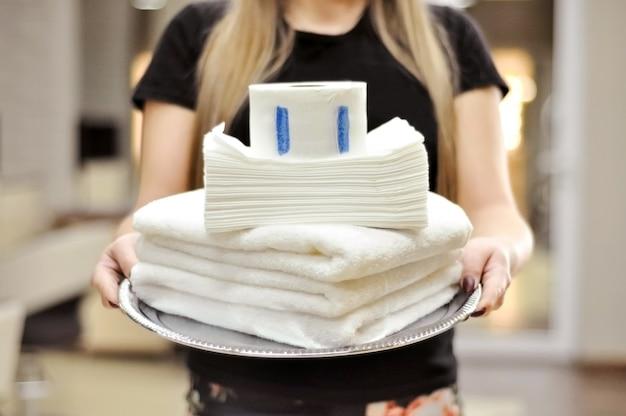 Handdoeken voor kapper. schoonheidssalon concept. witte katoenen handdoeken, wegwerp papieren handdoeken en wegwerp handdoeken, beschermende papieren kragen met plakstrip voor kappers op dienblad in vrouwelijke handen