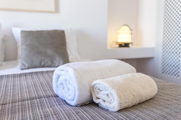 Handdoeken voor lichaam en voor handen op bed.
