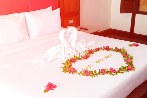Handdoekzwanen gevormd op luxebed met zonlicht, honey moon-bed