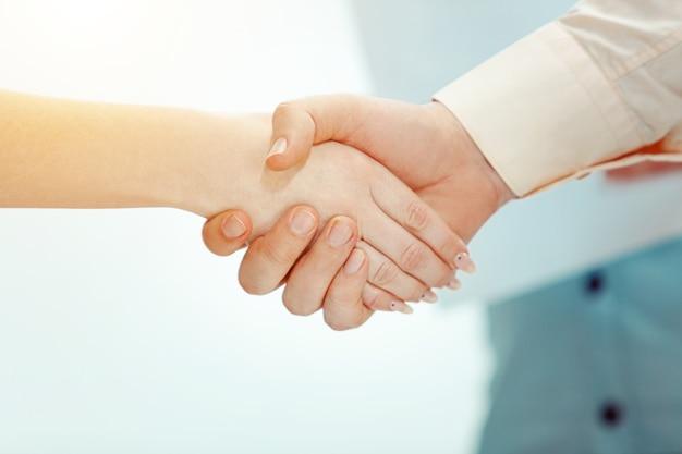 Handdruk. baas die jonge succesvolle werknemer van het bedrijf goedkeurt en feliciteert met haar succes en goede werk.