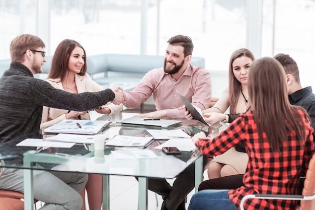 Handdruk financiële partners na de bespreking van een nieuw contract op de werkvloer op kantoor