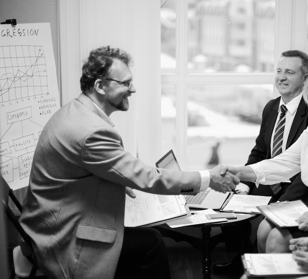 Handdruk financiële partners voorafgaand aan bespreking van de transactie. zwart-wit foto