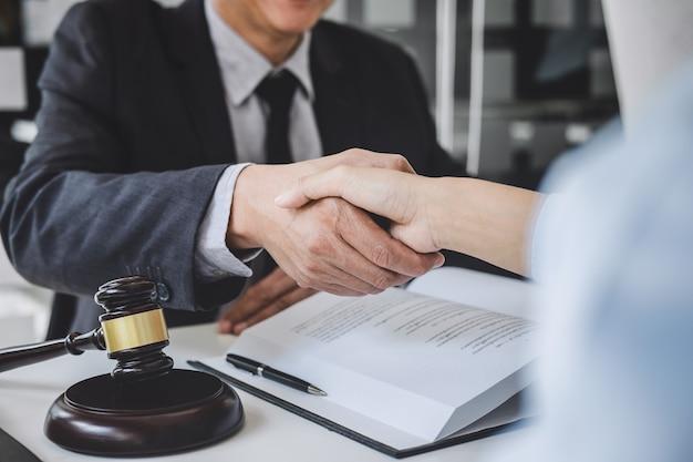 Handdruk na goede samenwerking, zakenvrouw handen schudden met professionele mannelijke advocaat na het bespreken van een goede deal van de overeenkomst in de rechtszaal, concepten van recht, rechter hamer met schalen van justitie