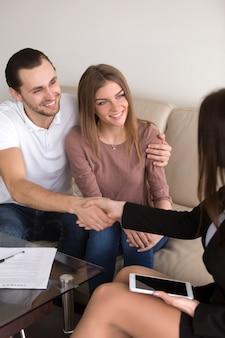 Handdruk na succesvolle overeenkomst, paar en vrouwelijk ondertekeningscontract, verticaal