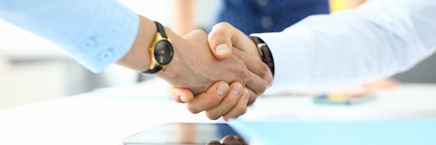 Handdruk tussen zakenman en zakenman tijdens bijeenkomst in kantoor