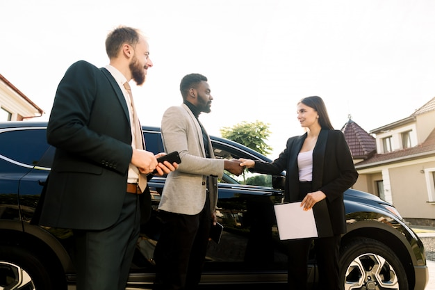 Handdruk van een klant, afrikaanse jonge zakenman en verkoper, jonge blanke vrouw op het erf van auto showroom buitenshuis. twee mannenpartners die nieuwe auto kopen