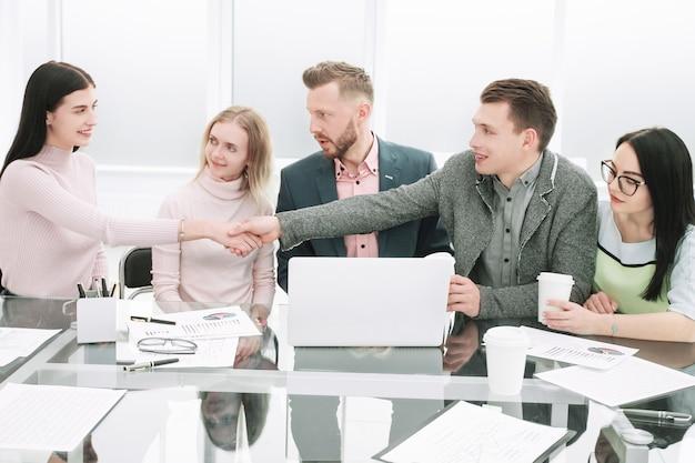 Handdruk van financiële partners tijdens een informele bijeenkomst op kantoor. concept van samenwerking