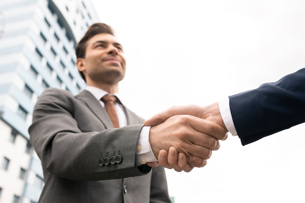 Handdruk van hedendaagse zakenpartners handen schudden buiten moderne architectuur