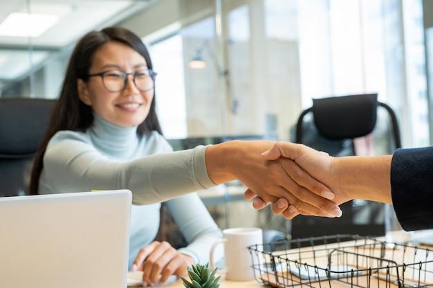 Handdruk van jonge gelukkig zakenvrouw met donker lang haar en haar nieuwe collega of zakenpartner over werkplek na het ondertekenen van papier
