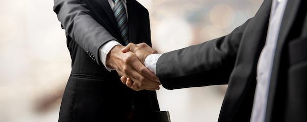 Handdruk van klant en investeerder of hand van succesvolle zakenmensen schudden de hand na succes in onderhandelen en contract-, partnerschap- en samenwerkingsconcept